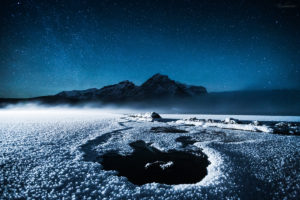 A cold night at Lake Minnewanka in mid-winter with car lights revealing a frozen landscape.