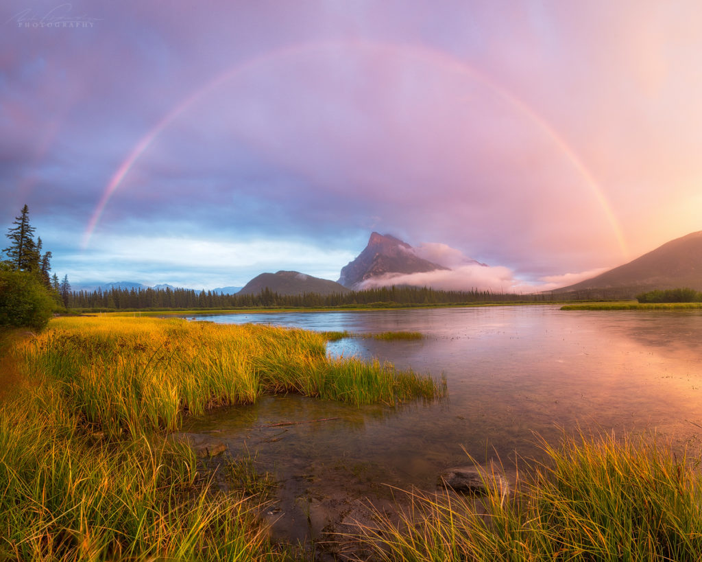 A complete rainbow forming over the top of Mt Rundle at Vermilion Lakes in Banff National Park