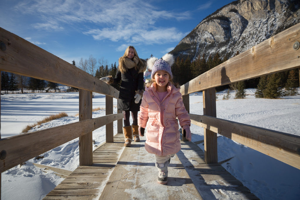 Running across one of the bridges at Cascade Ponds in Banff National Park as part of a family photography shoot on a winters day in banff National Park