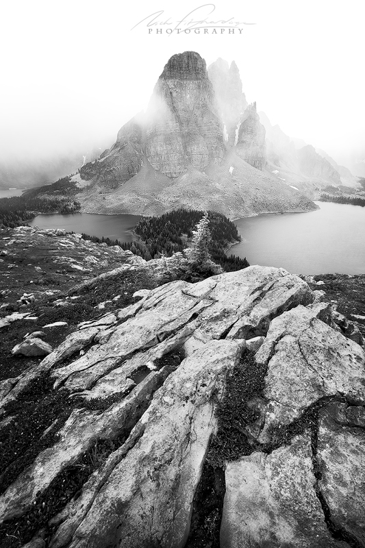 A black and white image of Sunburst Peak shrouded in fog from The Niblet.