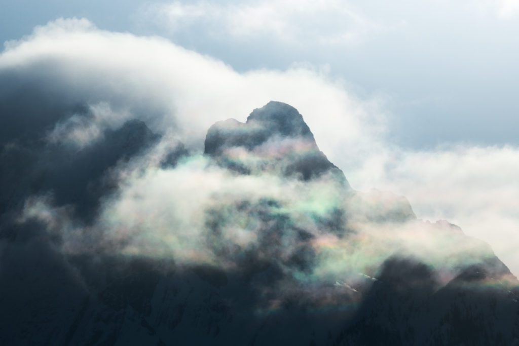 Cloud iridescence along the sharp edge of Mt Cory in Banff National Park