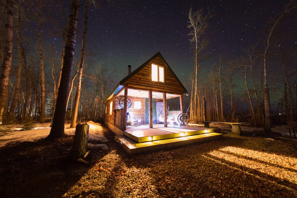 The aurora behind the Cabin in the Woods, La Crete, Alberta, Canada