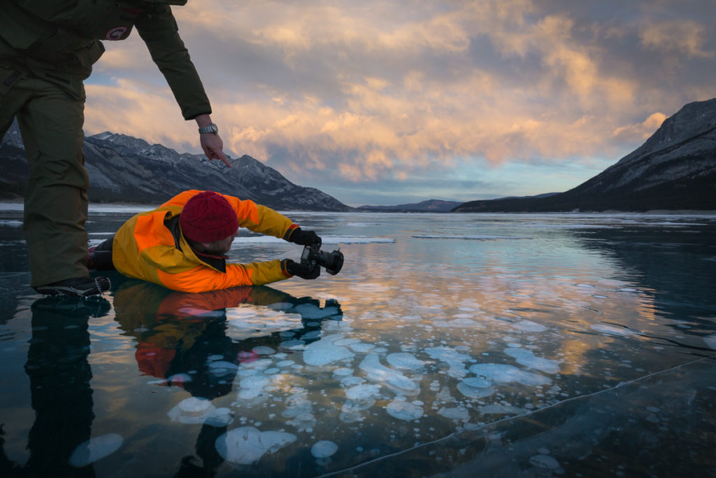Lieing down on the ice searching for a unique perspective of the ice bubbles at sunset, Abraham Lake, Alberta, Canada