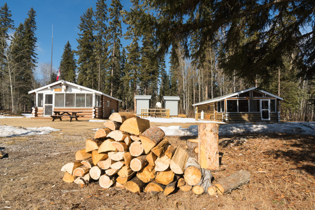 Patrol Cabin & Aurora Cabin with chopped wood in a sunny day in March, Wood Buffalo National Park, Alberta, Canada