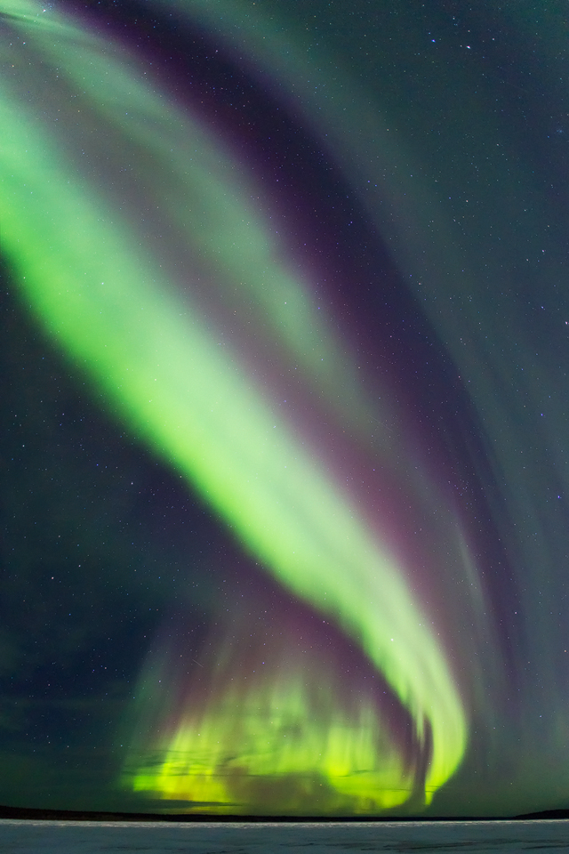 An auroral arc above a frozen Slave River, Fort Smith,Northwest Territories, Canada