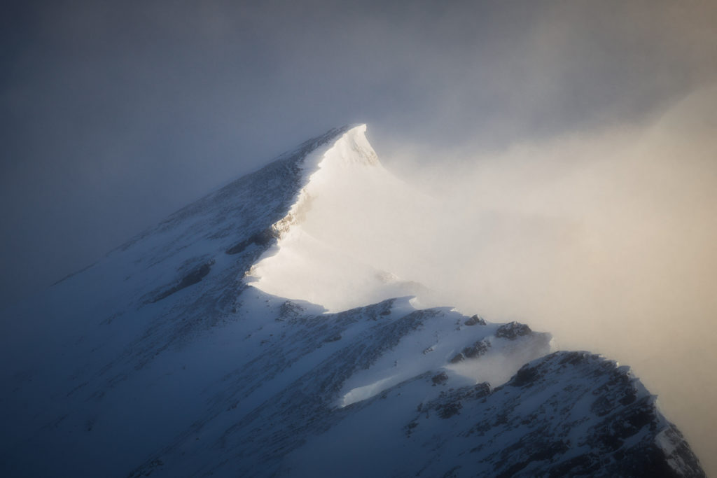 A telephoto view of a mountain summit getting hit with morning light and swirling snow clouds, Banff National Park, Alberta, Canada