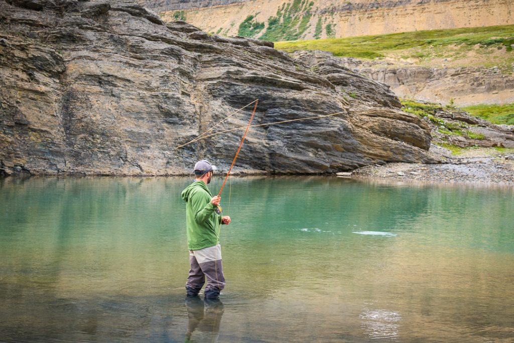 Fly fisherman casting while immersed in the lake with waders on, Alberta, Canada