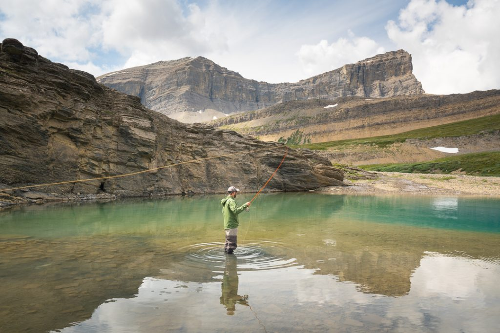 Fly fisherman casting in lower michelle lakes, Alberta, Canada