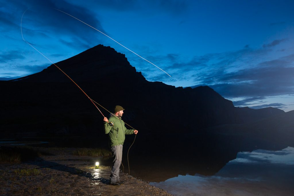 Fly fisherman casting line into the waters at night lit by strobe, Alberta, Canada