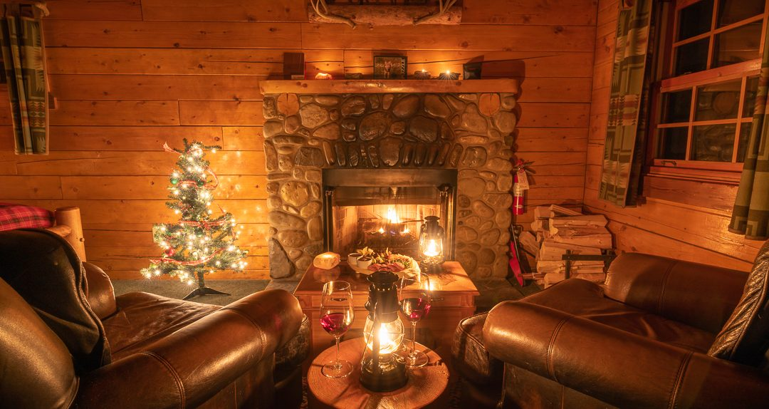 A festive indoor scene showing wine and a lit fireplace in one of the Baker creek Mountain Resort cabins.