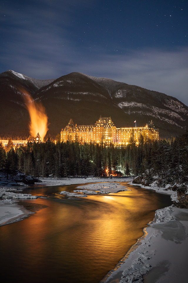 The Banff Springs Hotel from along the shores of The Bow River at night.