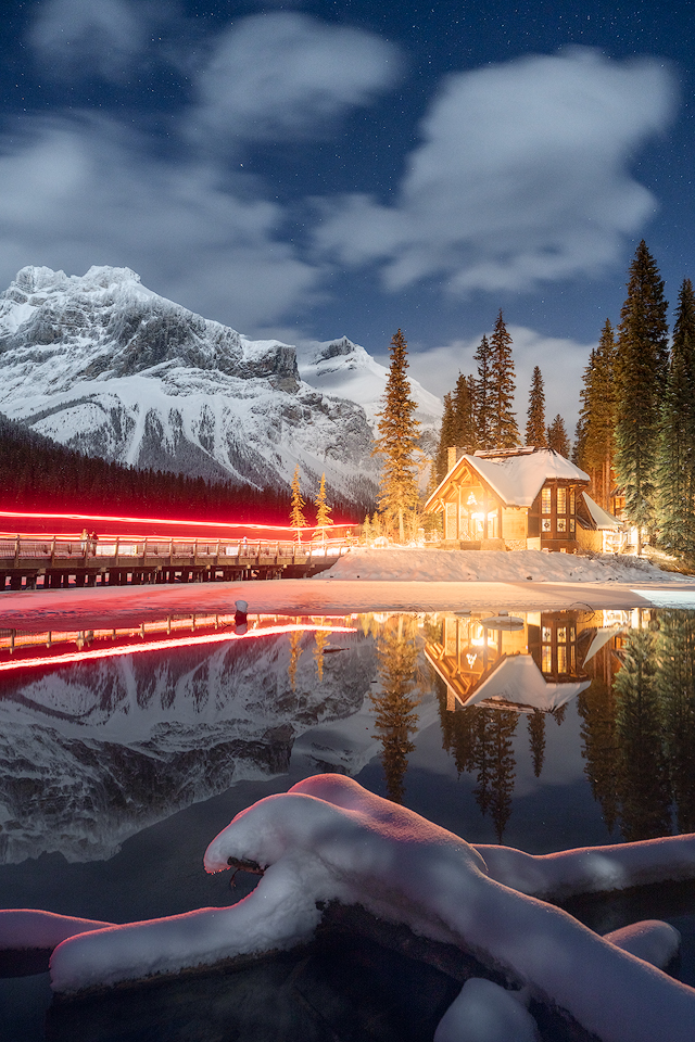 Emerald lake Lodge lit up at night in winter with traffic trails