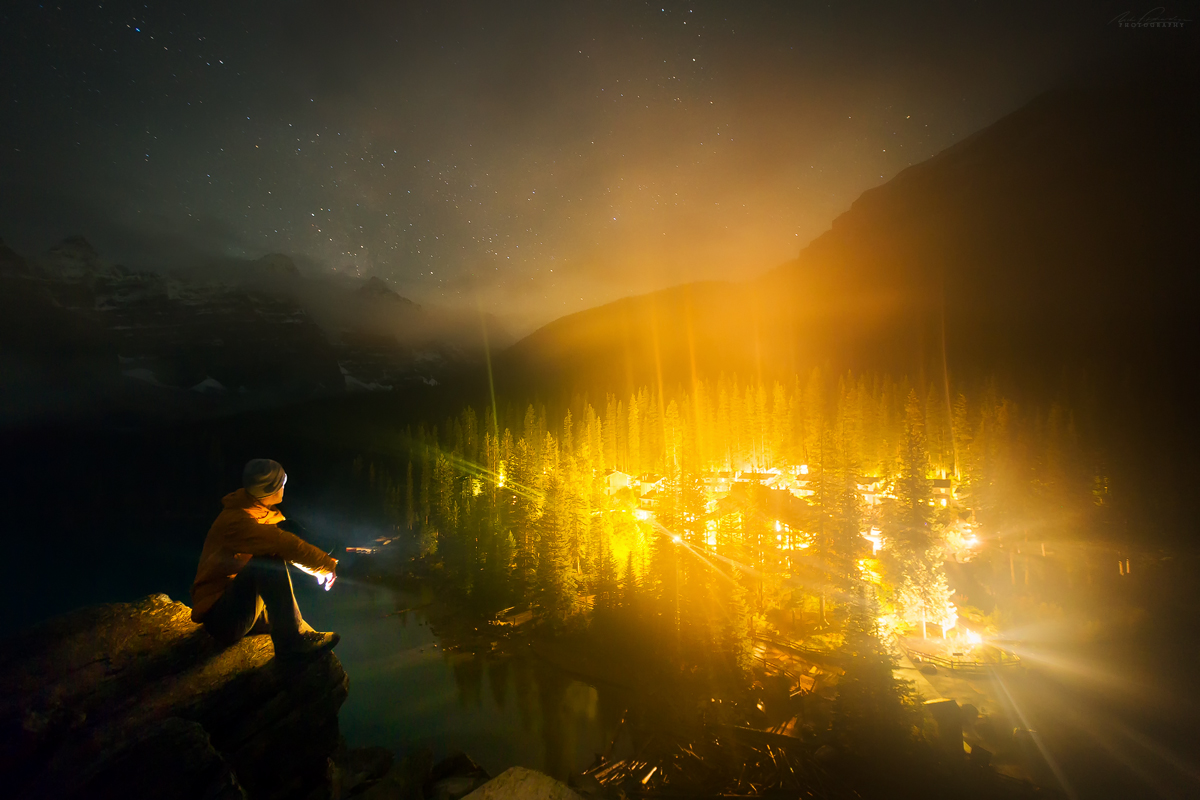 A lone observer looking at Moraine Lake Lodge from the rockpile at night. One of our Banff accommodation recommendations.