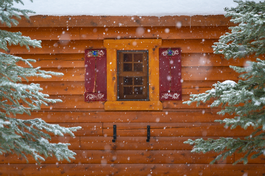 One of the windows on a Baker Creek Mountain Resort cabin with falling snow.