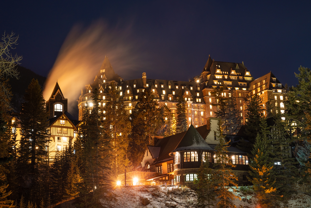 The Fairmont Banff Springs Hotel lit up on a winter night.