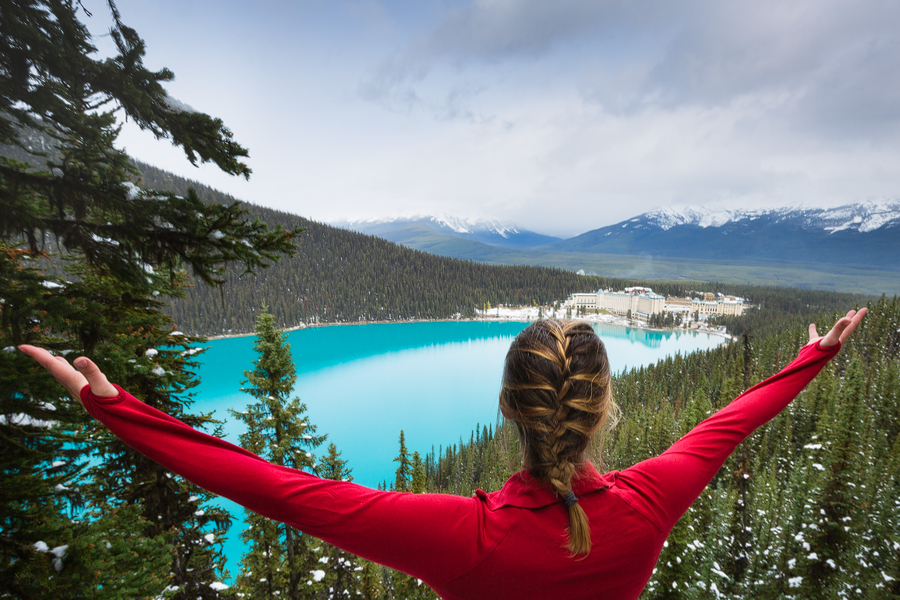 A young woman with a red shirt and arms outstretched looking at Lake Louise and the Fairmont Chateau lake Louise from Fairview Lookout. A great view of one of our recommended accommodations in the Banff area.