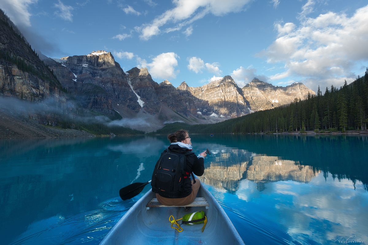 A young woman canoeing on Moraine Lake at sunrise in awe.