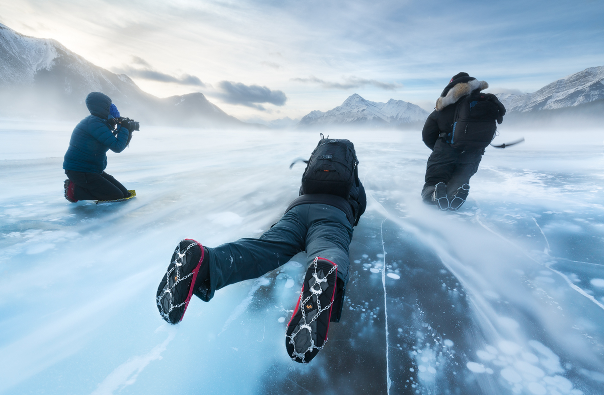A group of three photographers braving the wind on the surface of Abraham Lake wearing ice cleats and staying low.