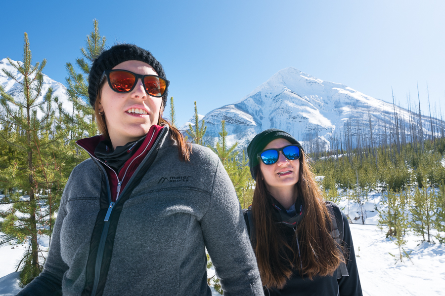 A couple of hikers wearing sunglasses on a sunny day along the Marble Canyon Trail in winter in Kootenay National Park.